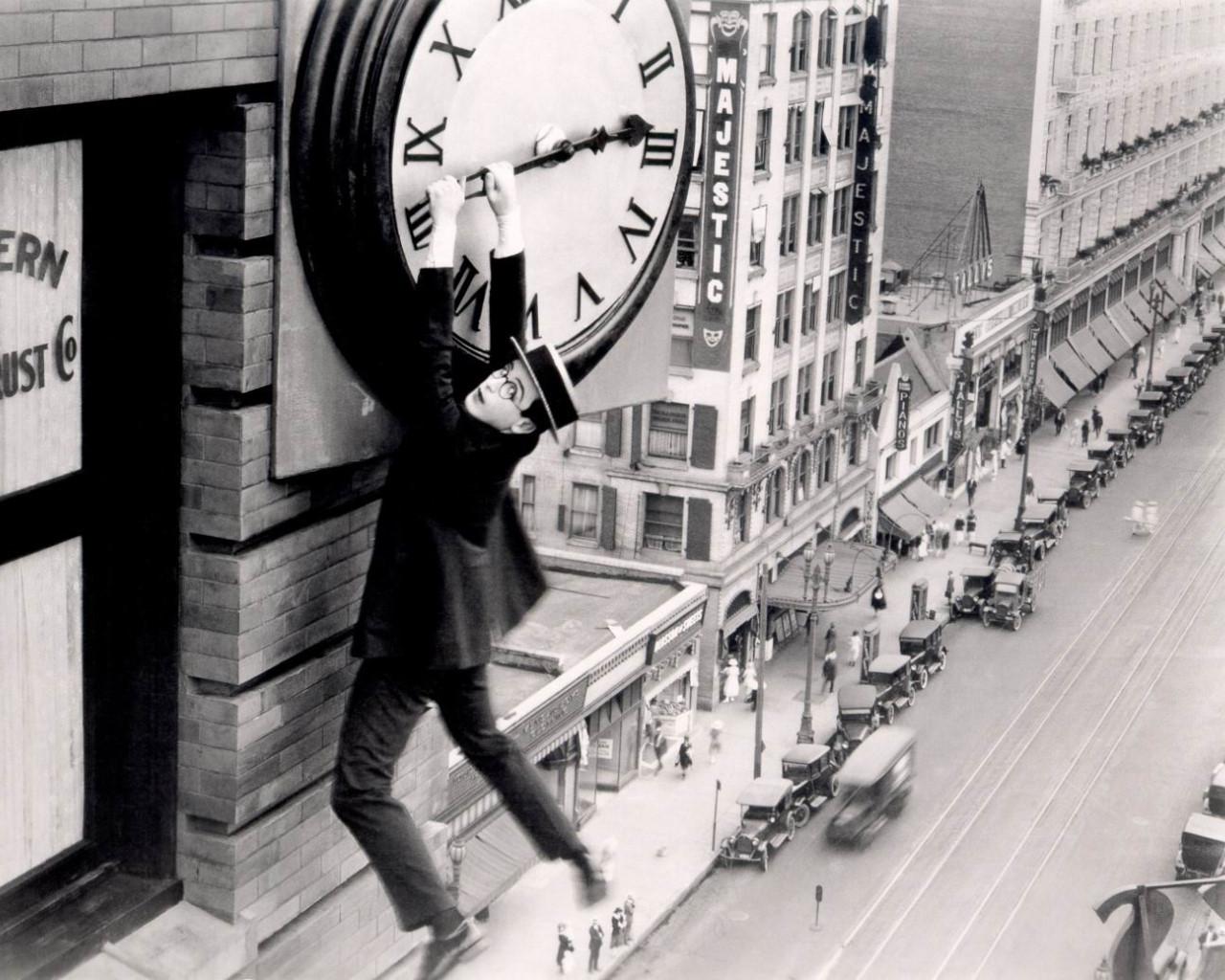 Hombre colgado de las agujas de un reloj en un edificio