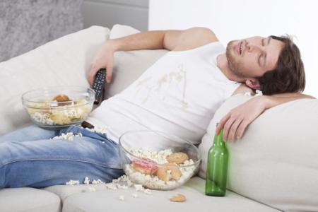 Hombre dormido en sofá con comida y bebida