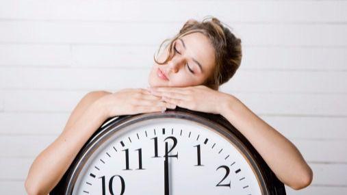 Mujer dormida sobre reloj