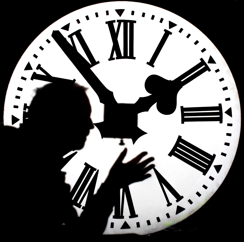sombra de un hombre frente a un reloj iluminado
