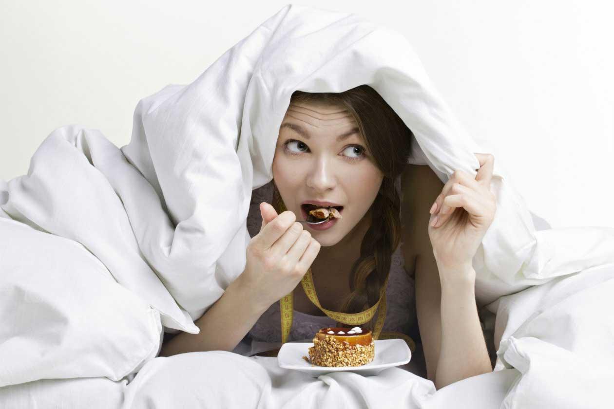 mujer come dulce en la cama. Dormir ¡la dieta de ensueño!